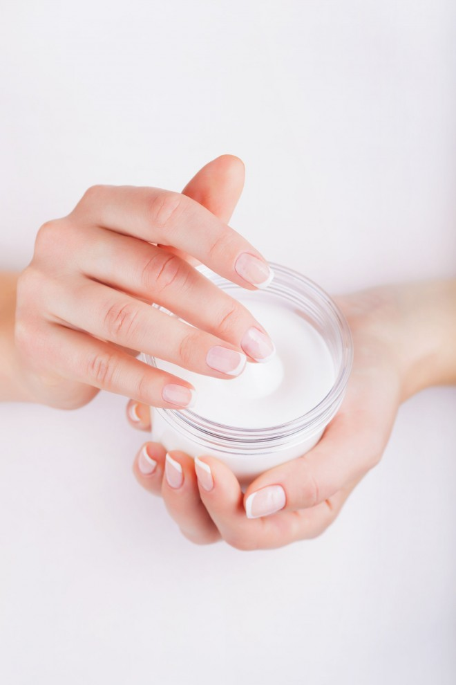 36734796 - woman applying cream on hands